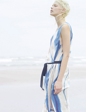 Woman in blue and white no sleeve dress stands on the seashore image photo.